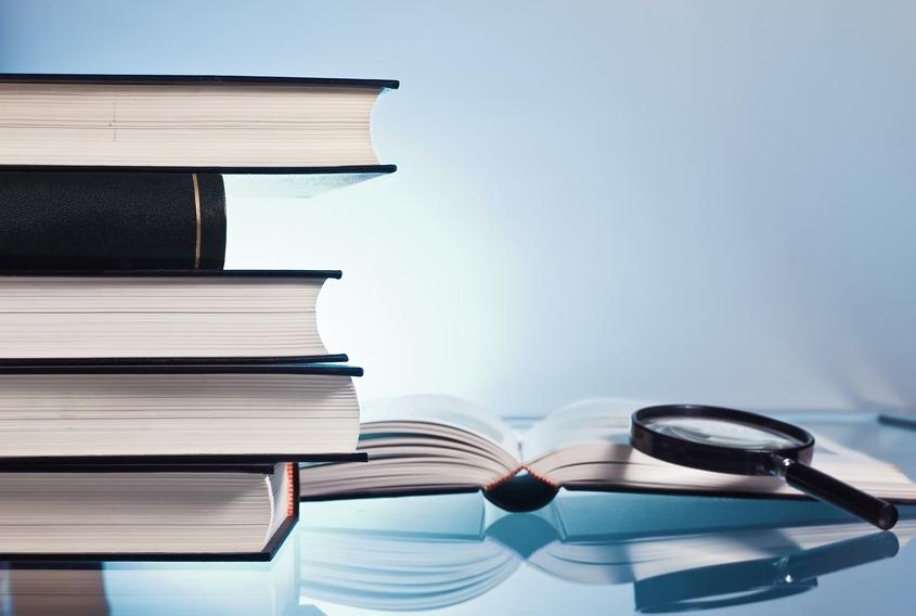 Un monton de libros junto a una lupa en un fondo azul